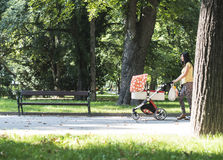 Mother walking in the park with baby buggy Stock Photos