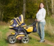 Mother walking with pram Stock Photo