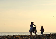 Mother walking with son. Silhouette of mother walking with son at seaside in the evening Stock Images