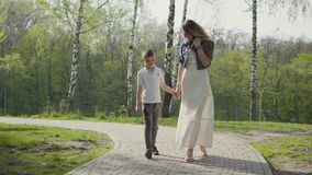 Mother walking with son in amazing green park. Outdoor recreation. stock video