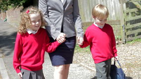 Mother Walking To School With Children On Way To Work Stock Photo
