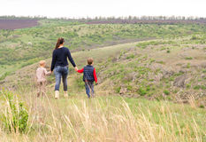 Mother walking with two boys in the countryside Stock Photo