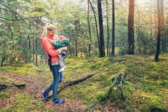 Mother walking in the woods with baby in kangaroo bag. Young mother walking in the woods with baby in kangaroo bag royalty free stock image