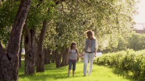 Mother walks with her daughter along the avenue of apple trees. The little girl is holding her mother by the hand. Child