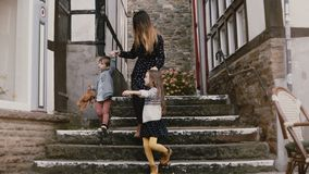 Mother walks with two children, holding hands. Woman, little boy and girl between amazing half-timbered houses. 4K. Mother walks with two children, holding stock video