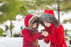 Mother warms hands of little daughter in snow in park. Mother warms hands of daughter in snow in park Stock Photography