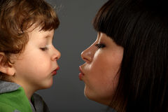 Mother was kissing her little son. Son looking on lips Stock Photos