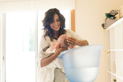 Mother washing baby in bath tub Stock Photos