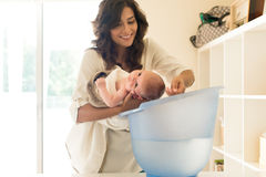 Mother washing baby in bath tub Royalty Free Stock Photography