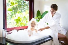 Mother washing baby in bubble bath. Water fun. Little child taking bubble bath in beautiful bathroom with big garden view window. Mother washing baby. Kids Royalty Free Stock Image