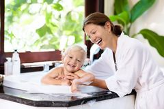 Mother washing baby in bubble bath. Water fun. Royalty Free Stock Image