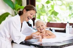 Mother washing baby in bubble bath. Water fun. Little child taking bubble bath in beautiful bathroom with big garden view window. Mother washing baby. Kids Stock Photo