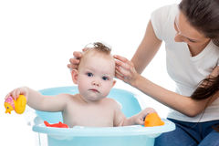Mother washing her baby girl in the bathtub with foam Royalty Free Stock Photo
