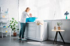 Mother washing her little child in plastic baby bathtub. At home stock photo
