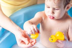 Mom washing little boy in a blue bath in the bathroom. Hygiene and the emotions of the baby while bathing. Mother washing little boy in a blue bath in the stock photo