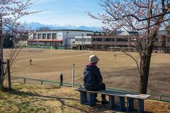 Mother watch son play baseball in school