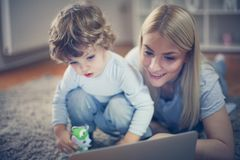 Mother watching cartoons with child in living room. Childhood stock photos
