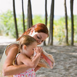Mother watching daughter blow into seashell stock image