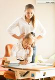 Mother watching at daughter doing homework Stock Photo