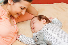 Mother watching her baby sleep. Young mother watching her baby sleeping peacefully with a teddybear Royalty Free Stock Image