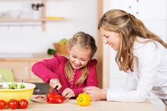 Mother watching her daughter prepare the meal. Mother watching her little daughter prepare the meal Royalty Free Stock Images