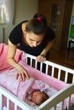 Mother watching her newborn sleeping child stock images