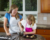 Mother watching over young daughter on how to make cookies Stock Images