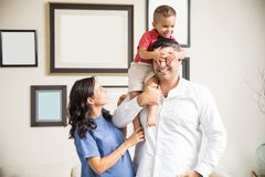 Mother Watching Playful Boy Covering Father`s Eyes At Home. Mid adult mother watching playful boy covering father`s eyes in living room at home royalty free stock images