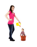 Mother watering baby in flower pot Royalty Free Stock Photo