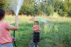 Mother watering her son with a hose umbrella playing in the rain. In the back yard on a summer day Royalty Free Stock Image