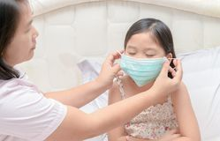 Mother wear protection mask daughter. To protect against influenza virus in bed room, health care and sick child concept Stock Photo