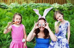 Mother Wearing Bunny Ears and Silly Eyes Poses with Children. A funny family portrait on Easter of a mother wearing bunny ears and holding up silly eyes made Royalty Free Stock Image
