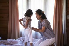 Mother wearing clothes for daughter stock image