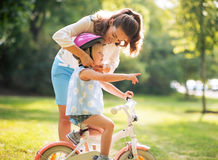 Mother wearing helmet on baby girl on bicycle Stock Images