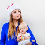 Mother wearing santa hat holding baby Stock Image