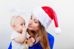 Mother wearing santa hat holding baby Stock Photo