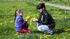 Mother weaves a wreath of dandelions for her daughter stock video