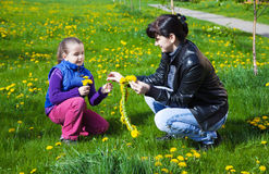 Mother weaves a wreath of dandelions for her daughter Stock Image