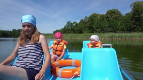 Mother wheel catamaran pedals. Two little children on back seats. Gimbal motion stock video footage