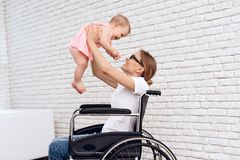 Mother in wheelchair play with newborn baby. royalty free stock photos