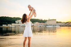 Mother which turns the child against a sunset and water. Happy mom and baby. Playing on beach. Young woman tossing up her son royalty free stock photos