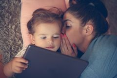 Mother whispered to her daughter on ear and using iPod. From above Royalty Free Stock Image