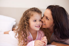 Mother whispering into her daughters ear Stock Photos