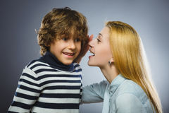 Mother whispering to son close up on gray background.  Royalty Free Stock Images