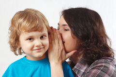 Mother whispers something to her little son. Mother whispers something to little son Royalty Free Stock Photo