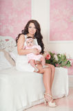 Mother in white dress sitting with baby on chair Royalty Free Stock Photos