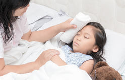 Mother wiped daughter`s body to reduce fever. Asian mother wiped daughter`s body to reduce fever in bedroom, concept of love and healthy care in family life stock images