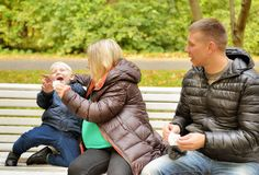 Mother wipes face scarf to child who sits on bench Stock Photography