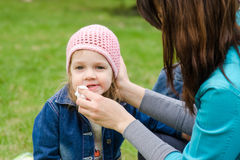 Mother wipes his mouth with a napkin girl on picnic Royalty Free Stock Photos