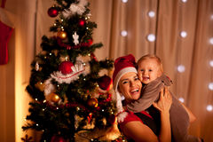 Mother With Beautiful Baby Near Christmas Tree Stock Photos